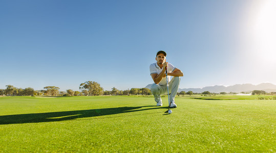 Pro golf player aiming shot with club on course
