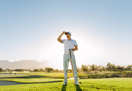 Male golfer holding golf club on field