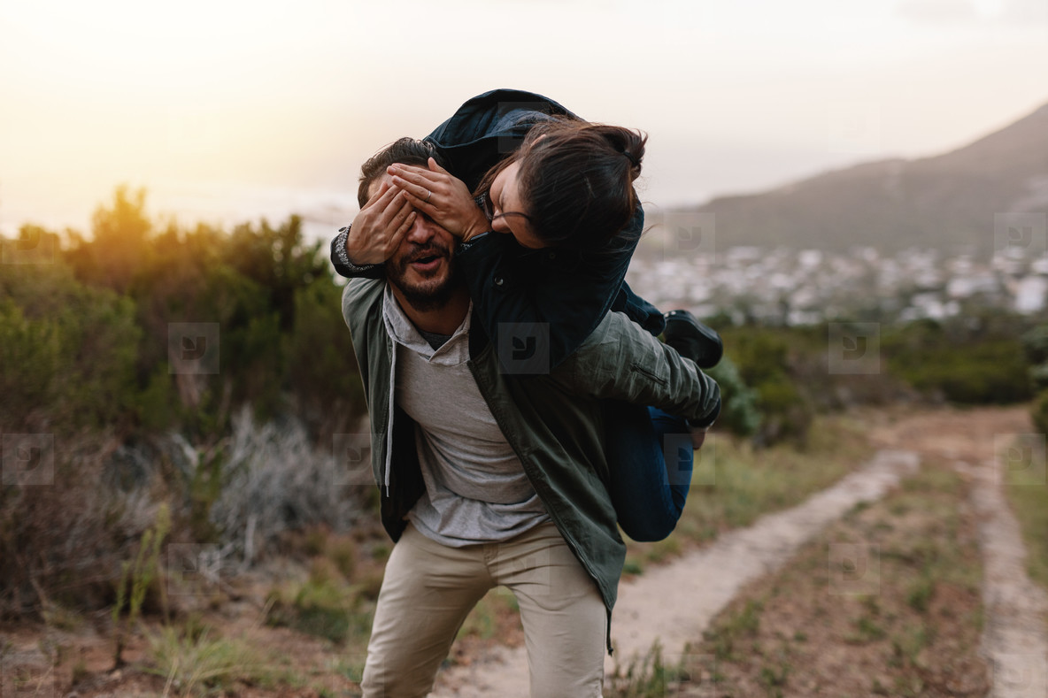 Playful young couple enjoying themselves in countryside