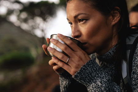 Female hiker taking rest and drinking coffee