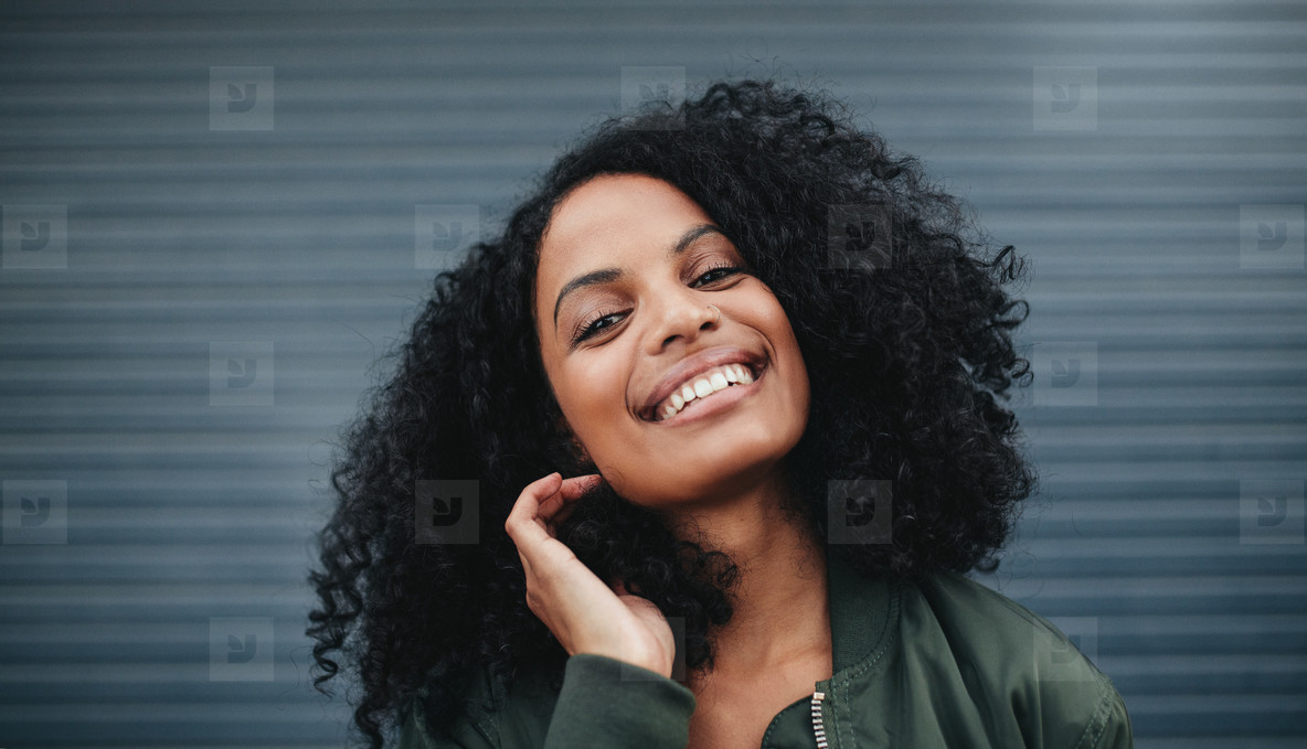 Beautiful african woman standing against gray background