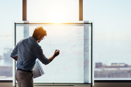 Entrepreneur putting his business ideas on whiteboard in boardro
