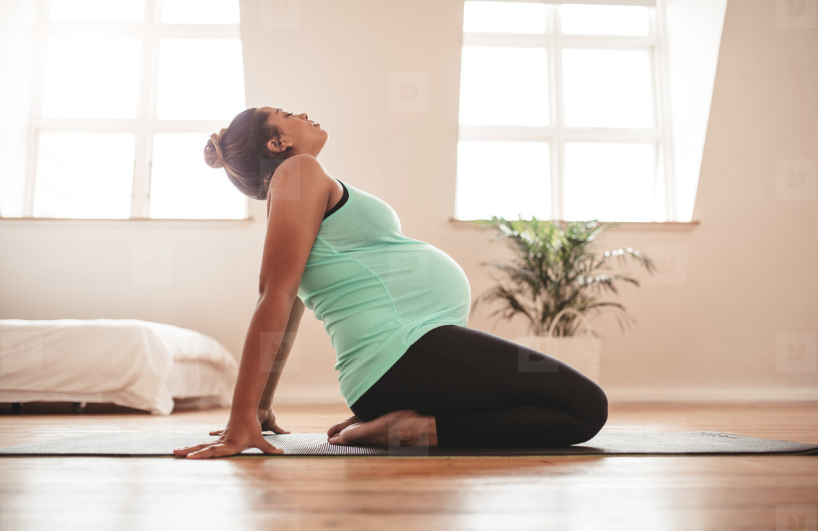 Expectant woman practising pregnancy yoga at home
