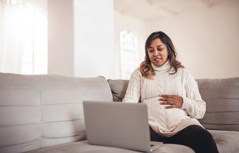 Beautiful pregnant woman with laptop sitting on sofa
