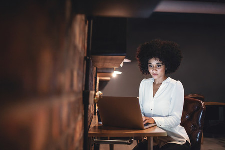 Young businesswoman working late on laptop in office