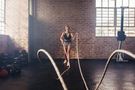 Athlete exercising in gym using heavy ropes