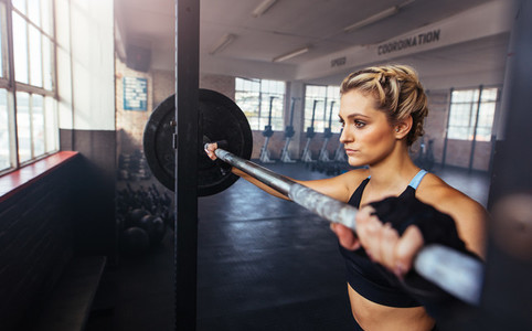 Young woman working out at the gymnasium using weight bar