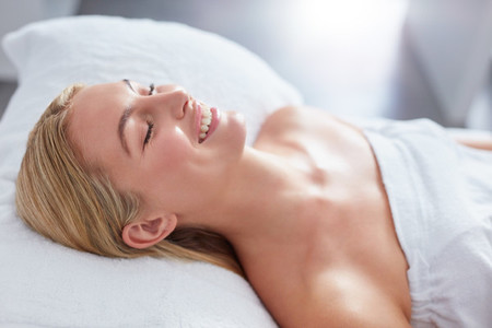 Smiling woman in a day spa relaxing on massage table