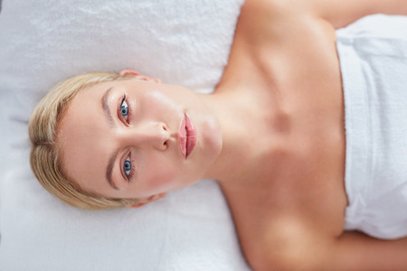 Pretty woman lying on massage table at dayspa