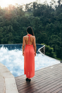 Woman standing by swimming pool at resort