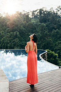 Young female model standing on the edge of pool
