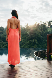 Woman standing at the poolside of holiday resort