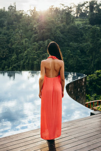 Young woman at poolside of a luxury resort
