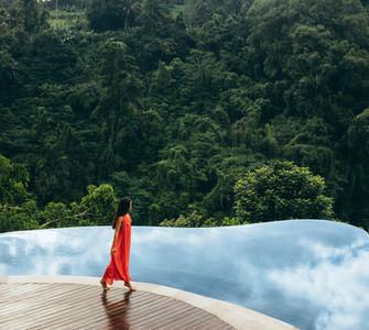 Woman walking on edge of infinity pool