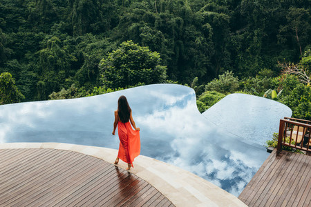 Woman walking near poolside of holiday resort