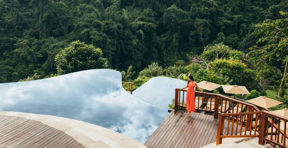 Woman near infinity swimming pool in nature