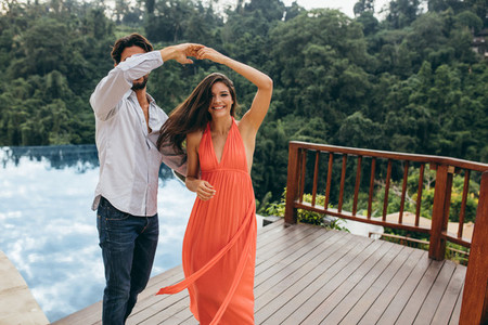 Couple in love dancing near swimming pool