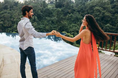 Caucasian couple dancing near swimming pool