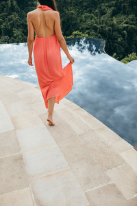 Woman in orange sundress walking along swimming pool