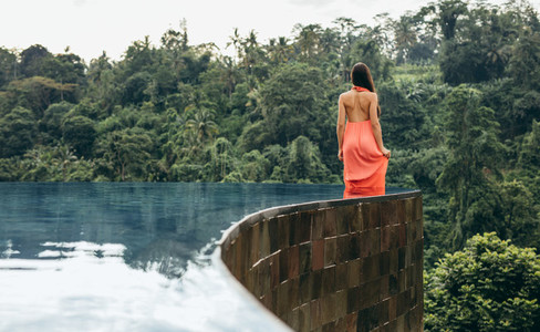 Young woman in infinity pool at luxury resort