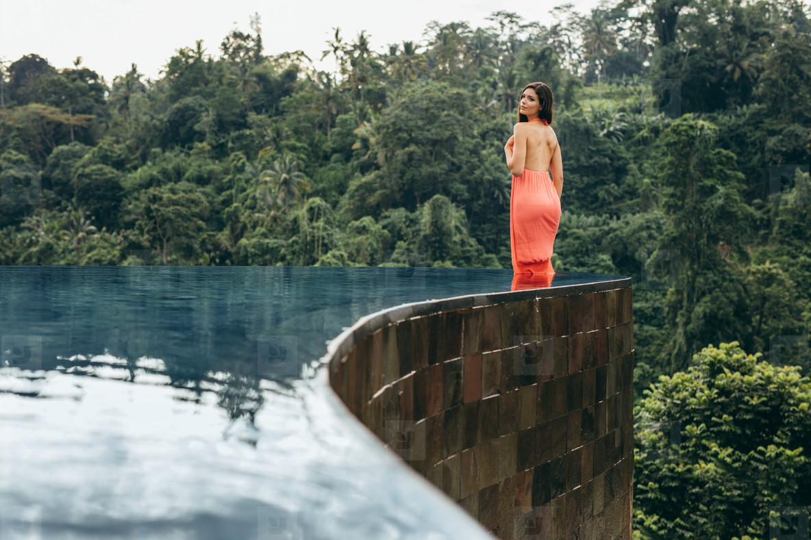 Attractive woman in infinity pool of holiday resort