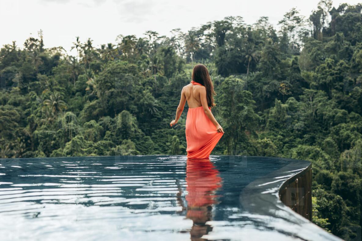 Female standing in swimming pool at luxury resort