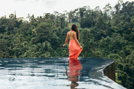 Female standing in swimming pool at luxury resort