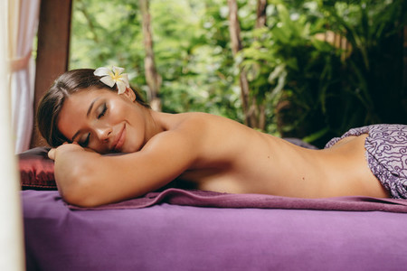 Woman lying on massage table in spa