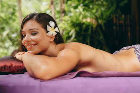 Attractive young woman lying on massage table