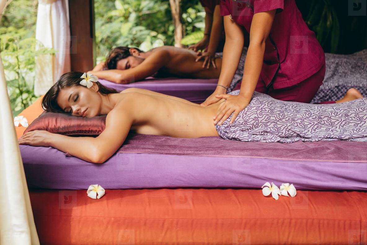 Couple at spa center having back massage