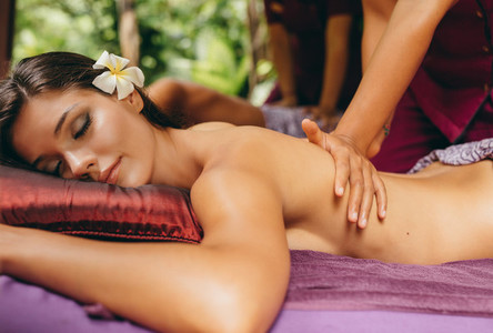 Young woman receiving back massage at day spa