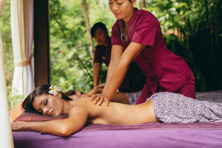 Massage therapist massaging woman at outdoor spa