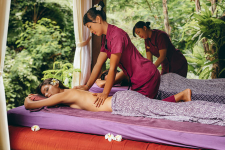 Couple having body massage at luxury resort spa center