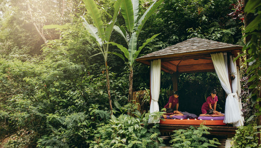 Massage pavilion in nature with couple receiving massage