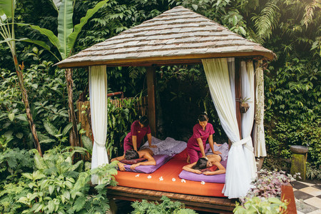 Couple receiving massage at outdoor spa