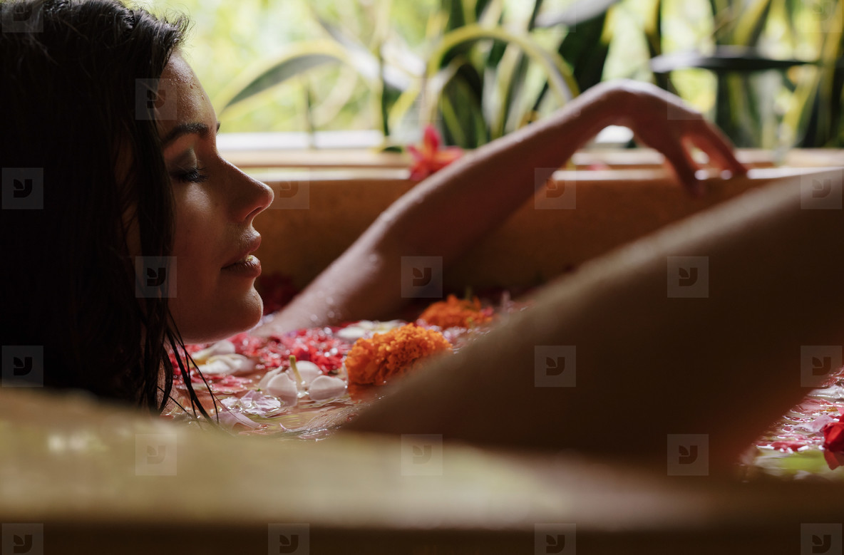 Woman relaxing in flower bath tub at day spa