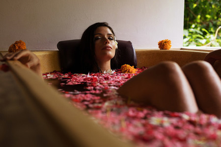 Attractive woman in bathtub with flowers