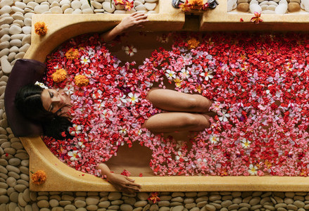 Woman having flower bath at health spa