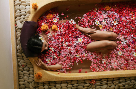 Woman in bathtub with petals