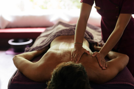 Man receiving back massage at health spa
