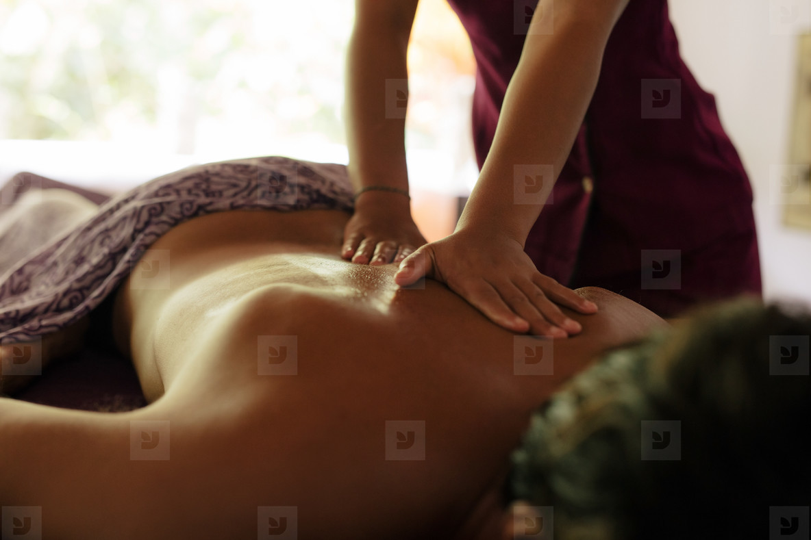 Masseuse massaging man at health spa