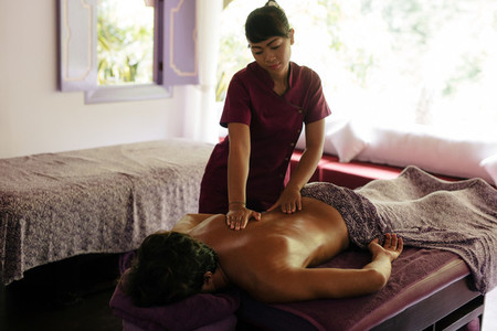 Female massage therapist massaging man at day spa