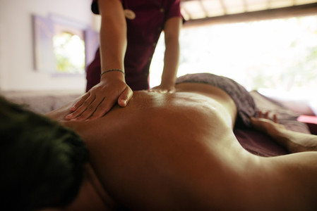 Female therapist massaging man at health spa