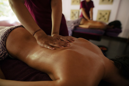 Masseuse massaging woman at health spa