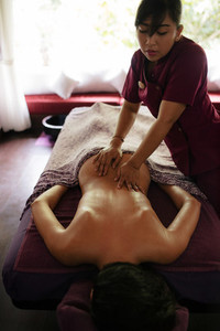 Woman getting back massage at spa resort