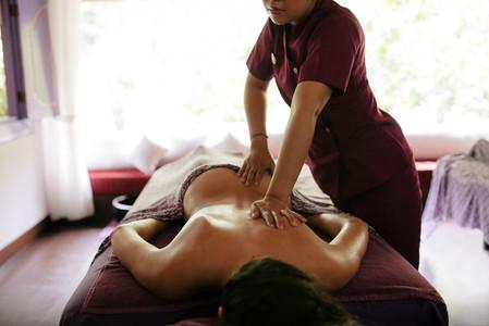 Massage therapist hands massaging back of a woman