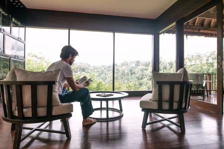 Man reading book in hotel room