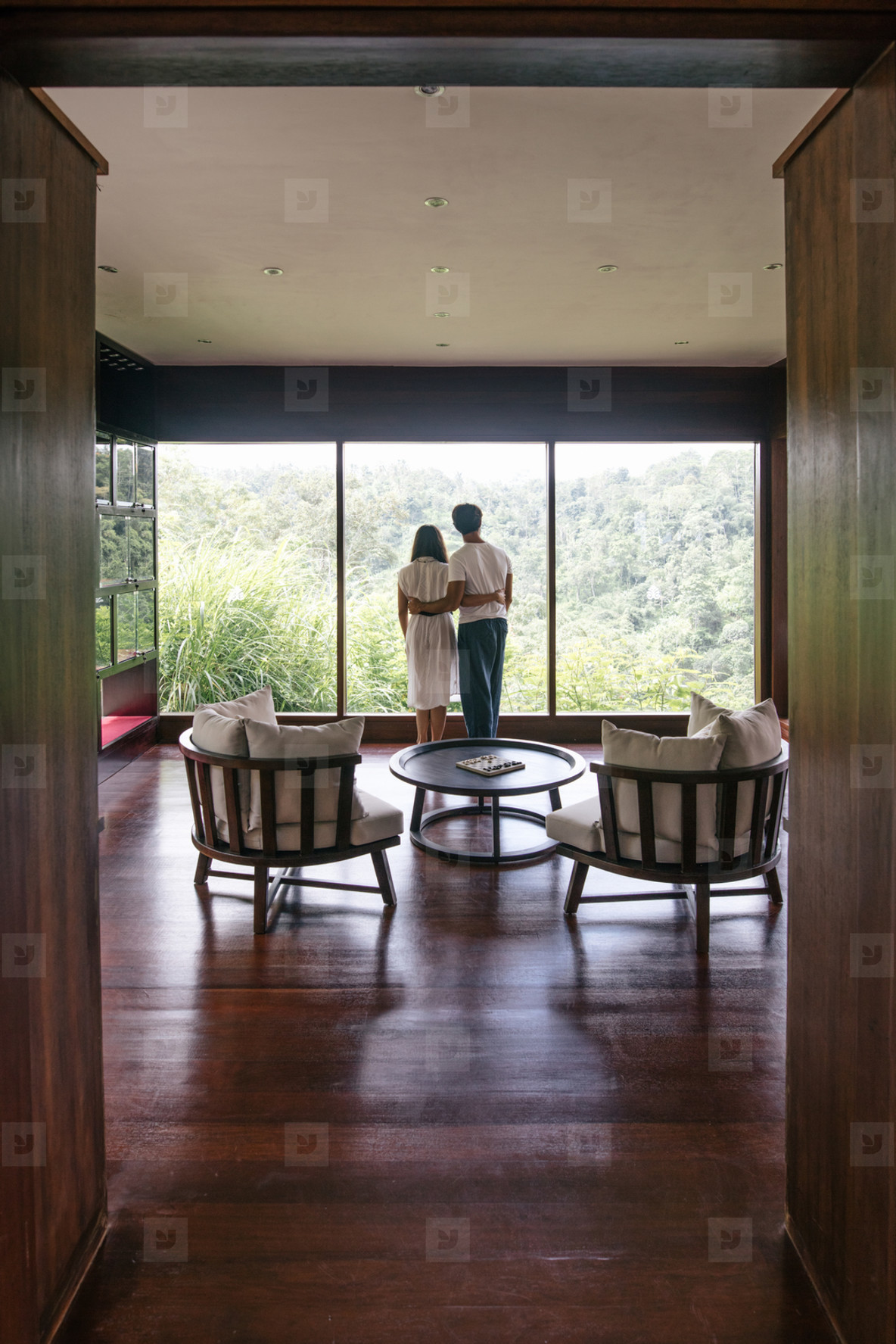 Couple in hotel room enjoying view from window