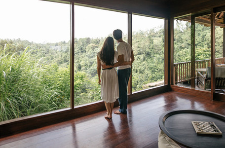 Couple standing by window and looking at landscape