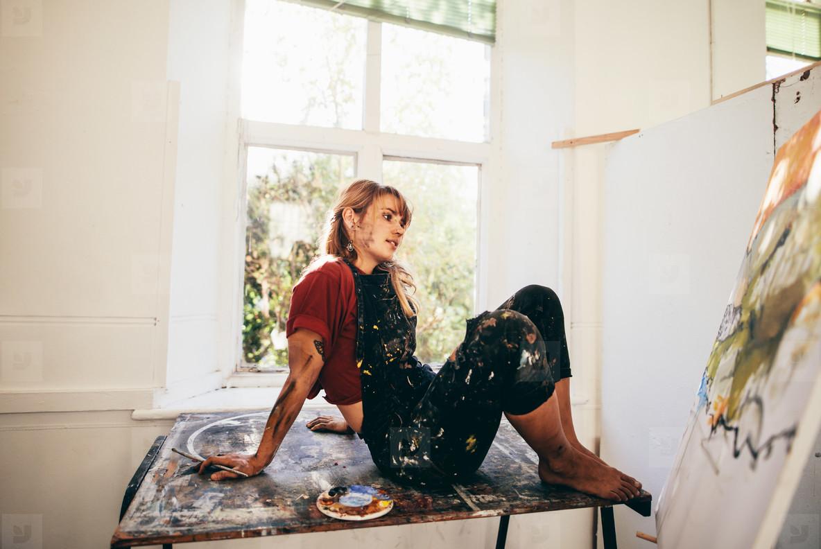 Pensive female painter working in studio